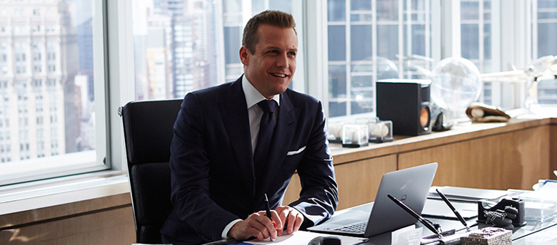 Harvey Specter sentado na mesa do escritório