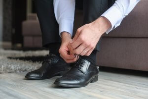 homem amarrando sapato social derby preto