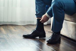 homem ajeitando a meia do sapato social