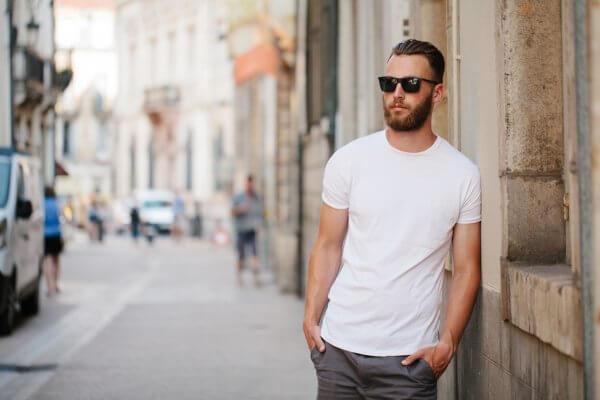 homem de camiseta branca e óculos de sol na rua