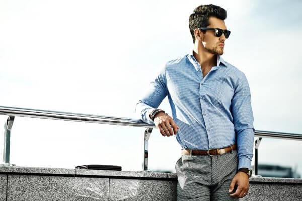 homem na rua de camisa social azul e óculos de sol