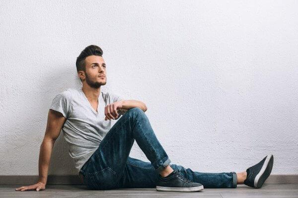 homem sentado de camiseta cinza, calça jeans e tênis casual