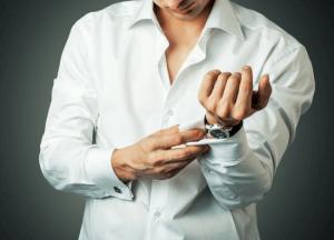 homem ajustando camisa social branca
