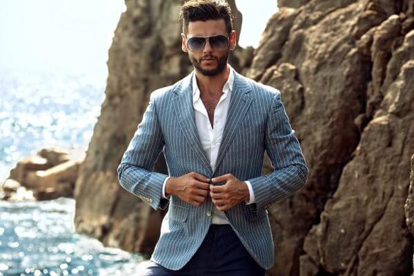 homem nas montanhas com blazer azul listrado, camisa social branca e óculos de sol