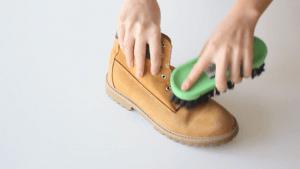 homem escovando calçado em couro