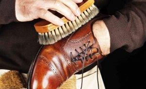 homem esfregando escova no sapato de couro liso marrom