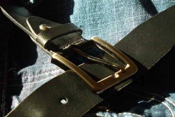 close na fivela de metal de um cinto de couro preto em cima de uma calça jeans