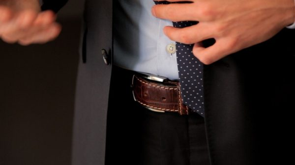 close na fivela de um cinto de couro marrom de um homem usando camisa social e blazer por cima