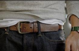 close no cinto de um homem usando calça jeans e camiseta cinza